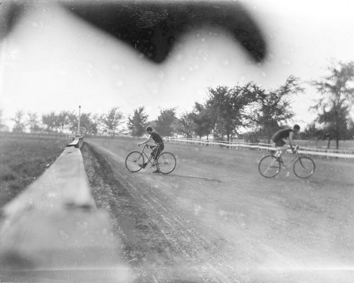 Two unidentified boys riding bicycles on race trackGeorge Silas Duntley Photographs 1899-1918
