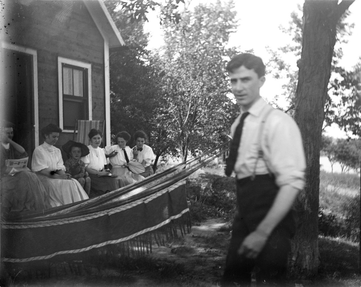 Unidentified man in foreground, five women and boy sitting on porch with hammock in backgroundGeorge Silas Duntley Photographs 1899-1918