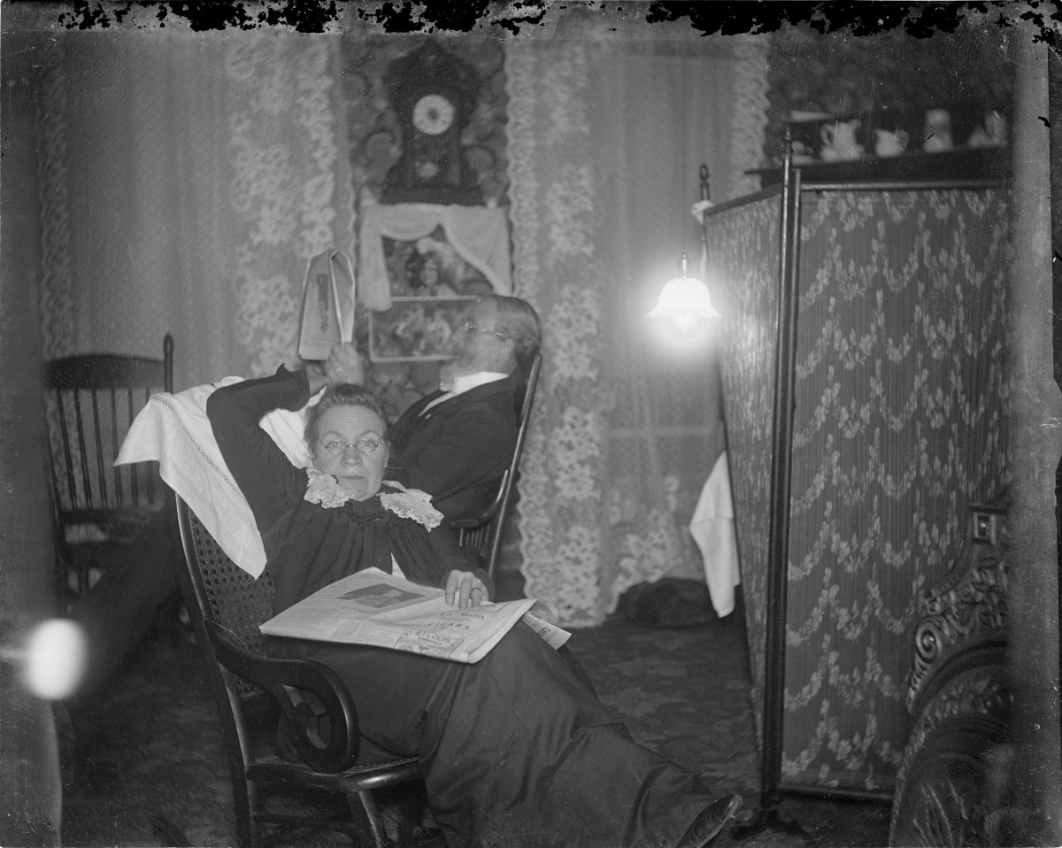 Woman sitting in rocking chair with newspaper on lap and man seated behind herGeorge Silas Duntley Photographs 1899-1918