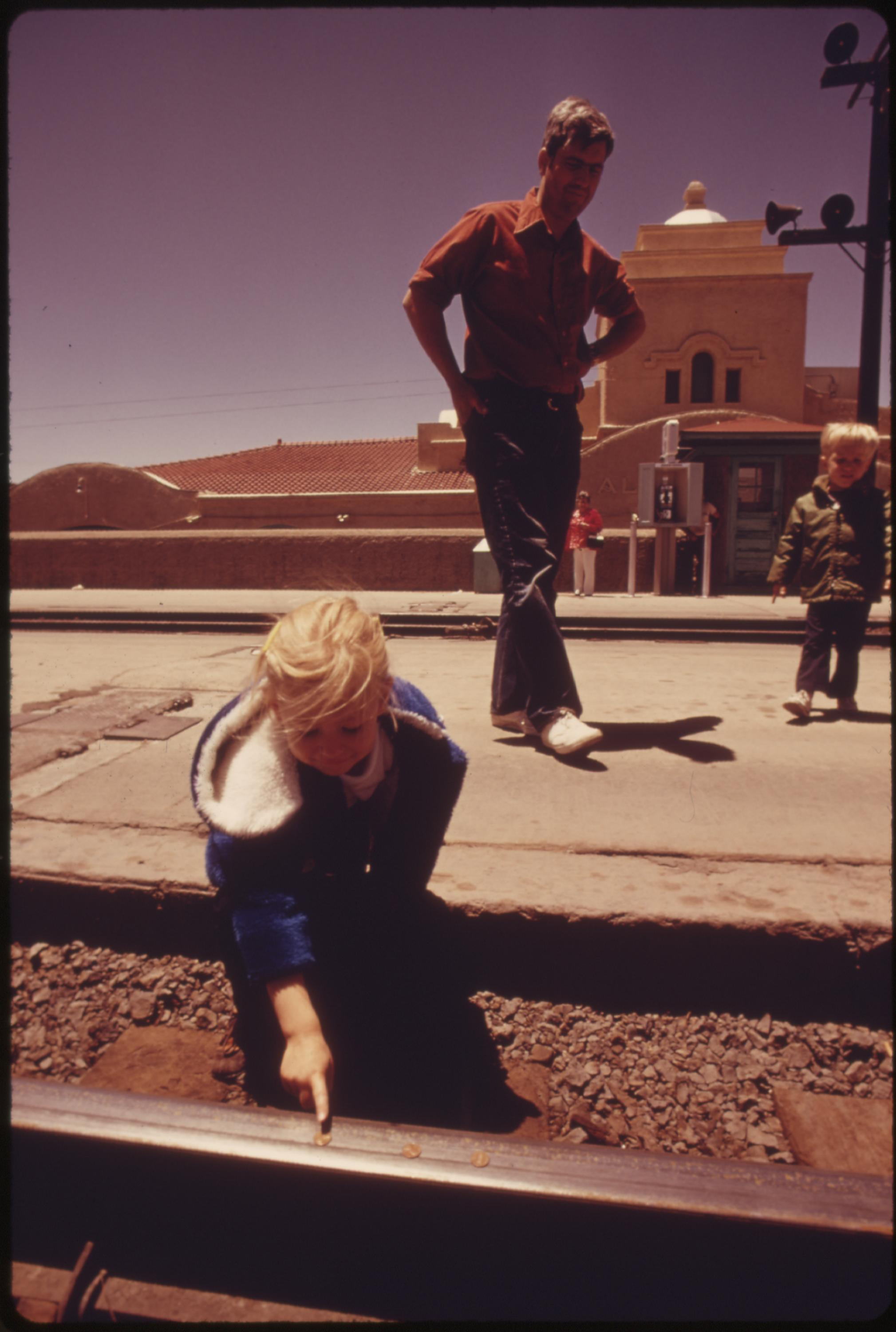 A child places pennies on the track at the Albuquerque, New Mexico, train station and will wait for the Southwest Limited to flatten them as a souvenir, June 1974