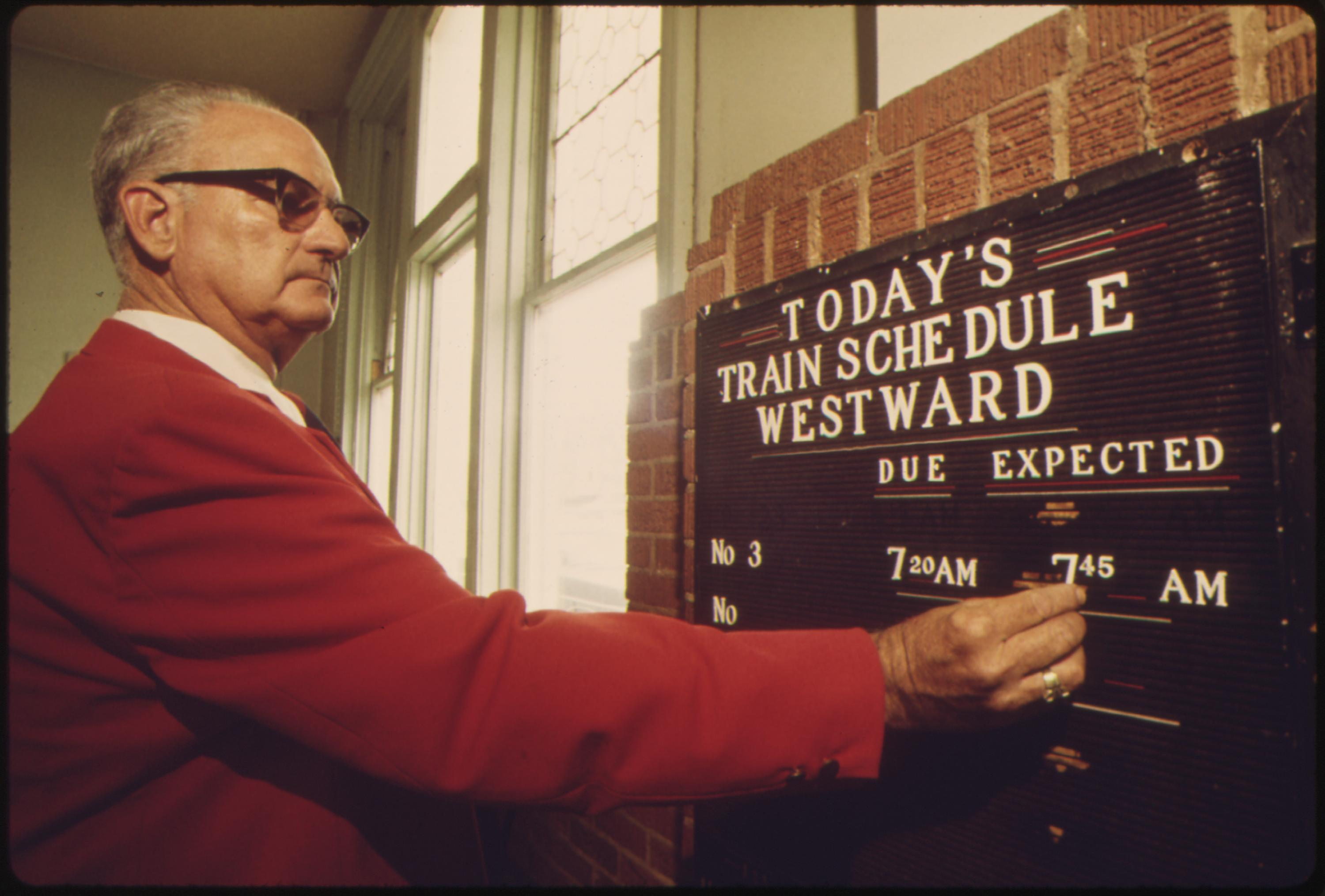 Amtrak station agent at Dodge City, Kansas, places the expected arrival time of the westbound Southwest Limited on a schedule board as part of his duties, June 1974