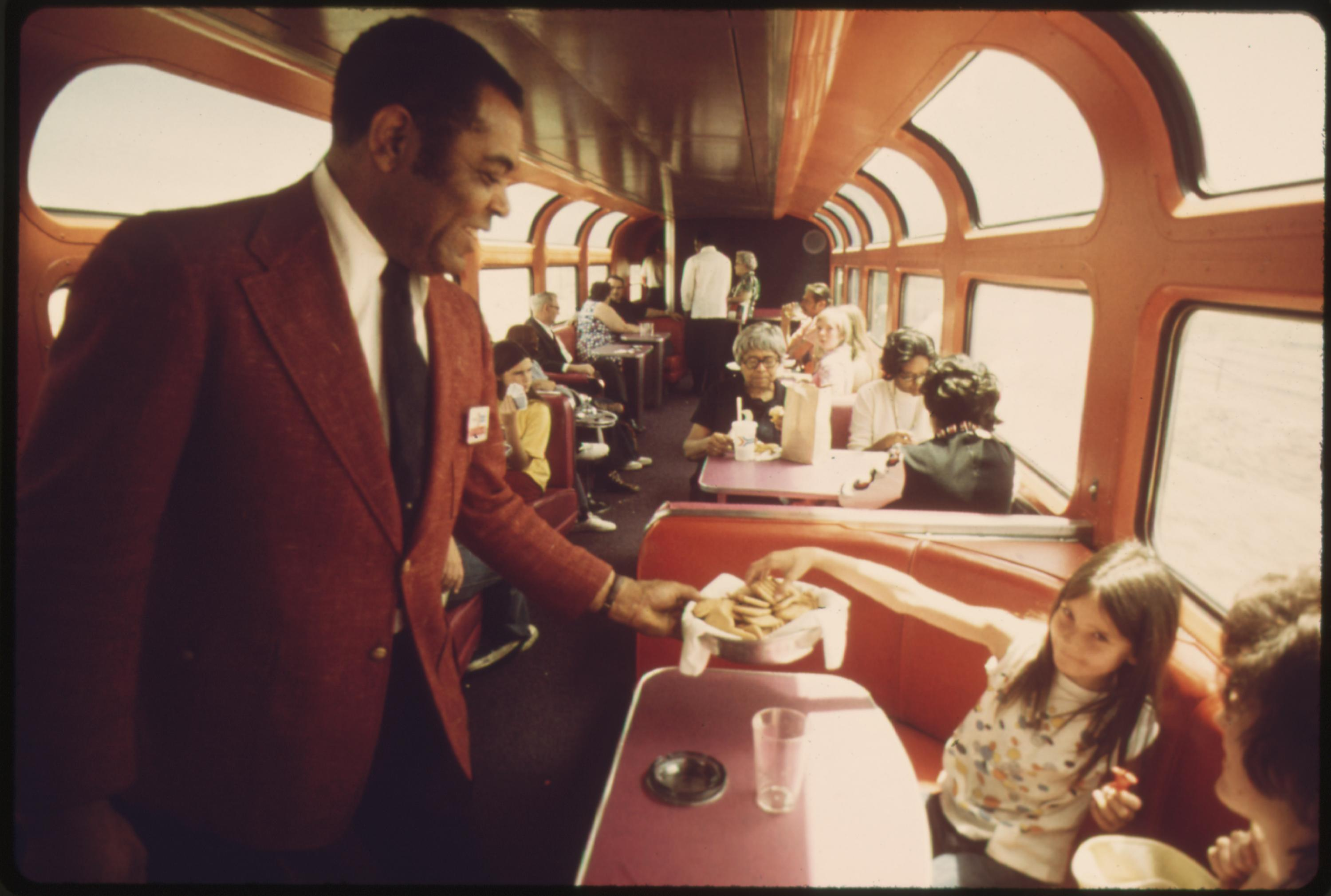 An Amtrak passenger service director serves cookies to passengers in the lounge car of the Southwest Limited enroute from Albuquerque, New Mexico, to Dodge City, Kansas, June 1974
