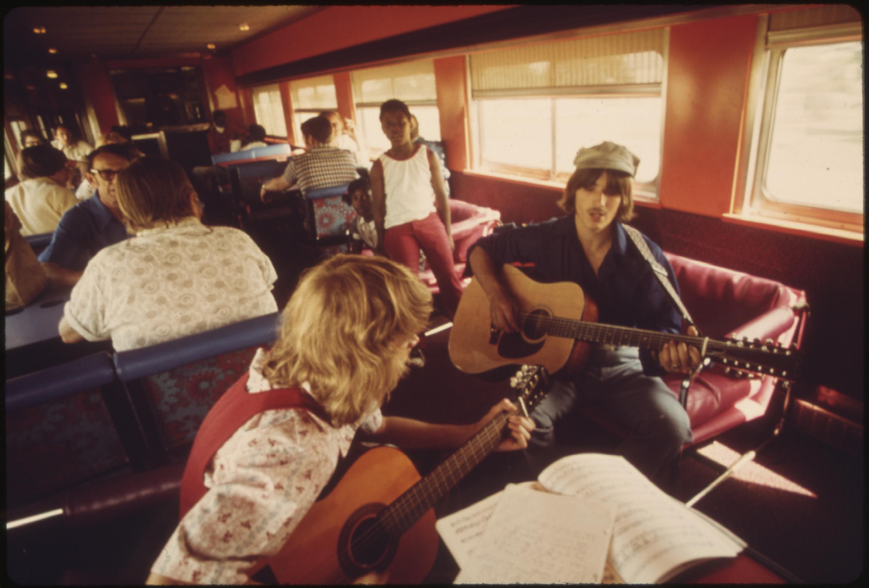 An impromptu guitar session provides a little music for passengers in the lounge car of the Lone Star as it crosses Oklahoma enroute from Chicago to Houston, Texas, June 1974