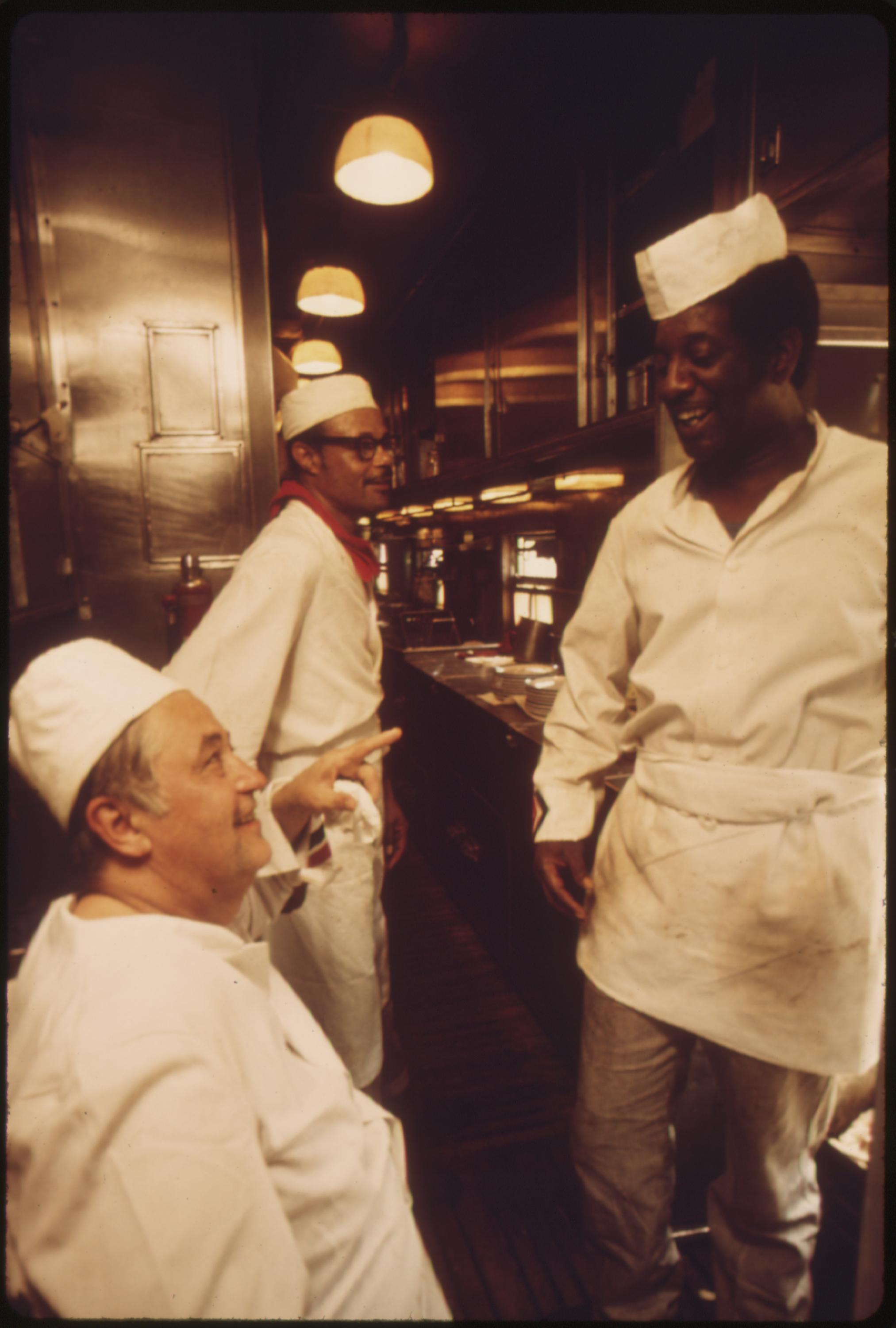 Chef and cooks in the galley of the Lone Star take a brief rest from their duties of feeding the passengers as the train speeds across Oklahoma enroute between Chicago and Houston, Texas, June 1974