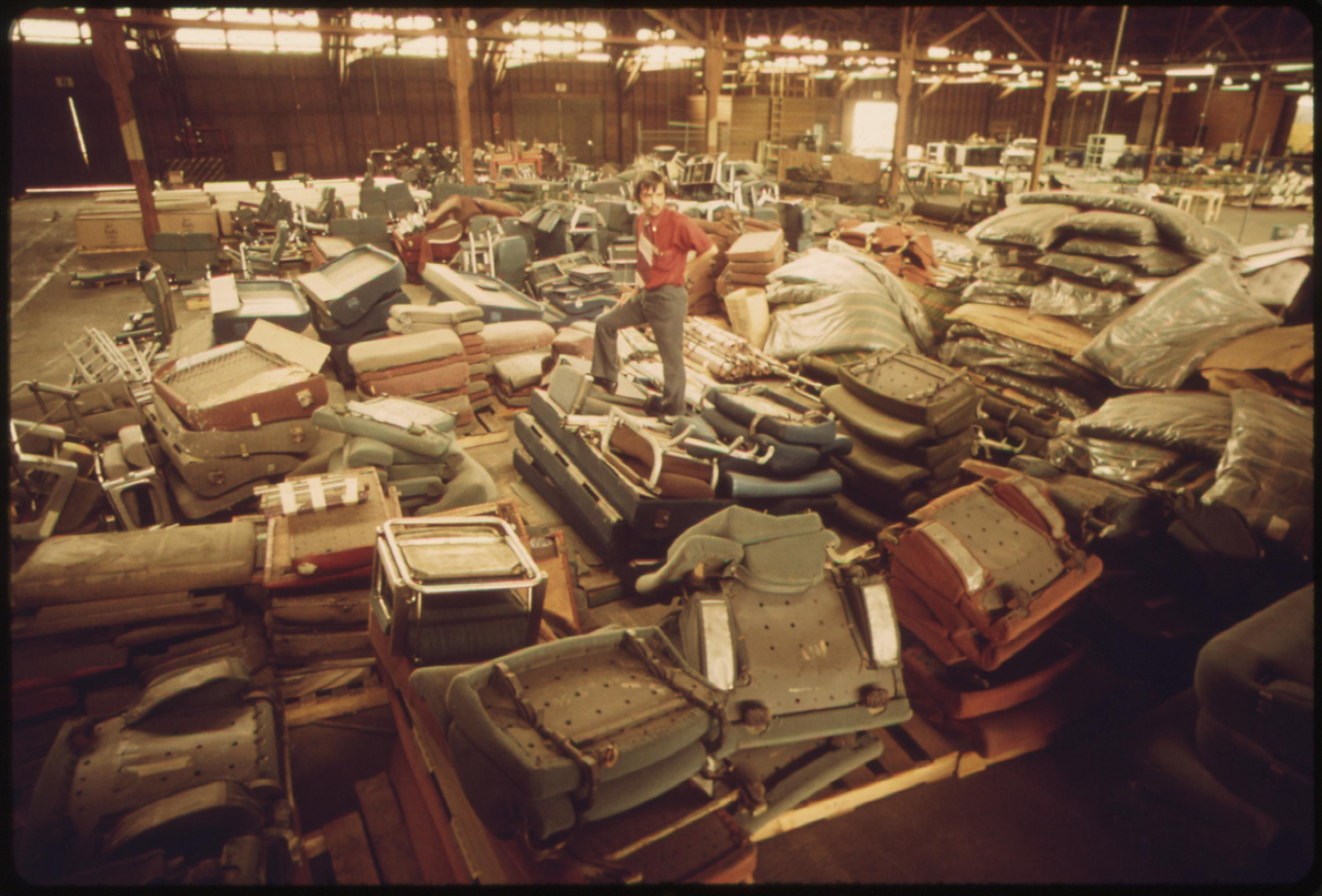 Old equipment from Amtrak passenger cars is piled in a warehouse, May 1974