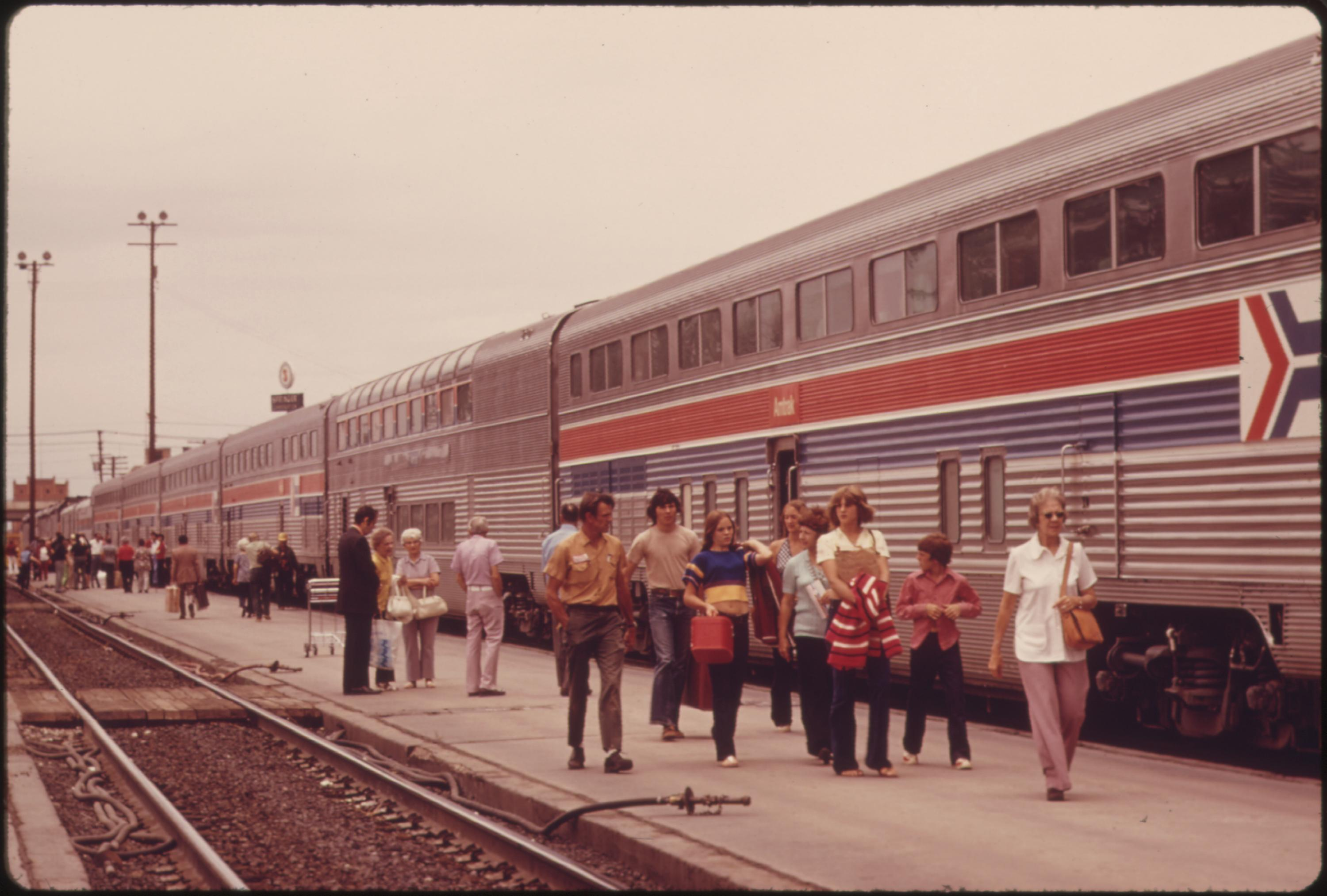 Passengers of the Southwest Limited strolling beside the Amtrak train at Albuquerque, New Mexico, as it halts for refueling enroute to Chicago from Los Angeles, California, June 1974