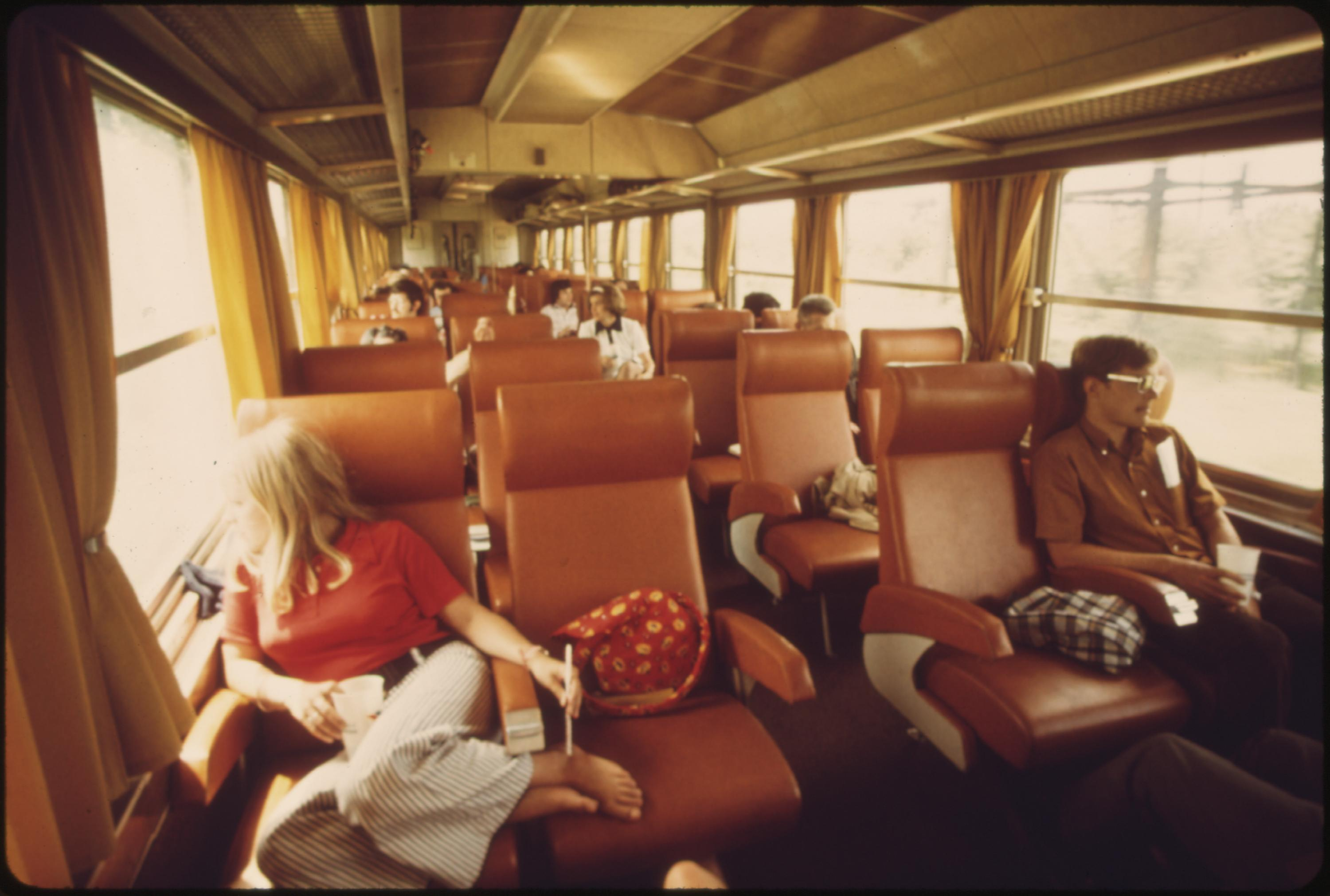 Passengers view the scenery between St. Louis, Missouri, and Chicago, Illinois, on the Amtrak turboliner, June 1974