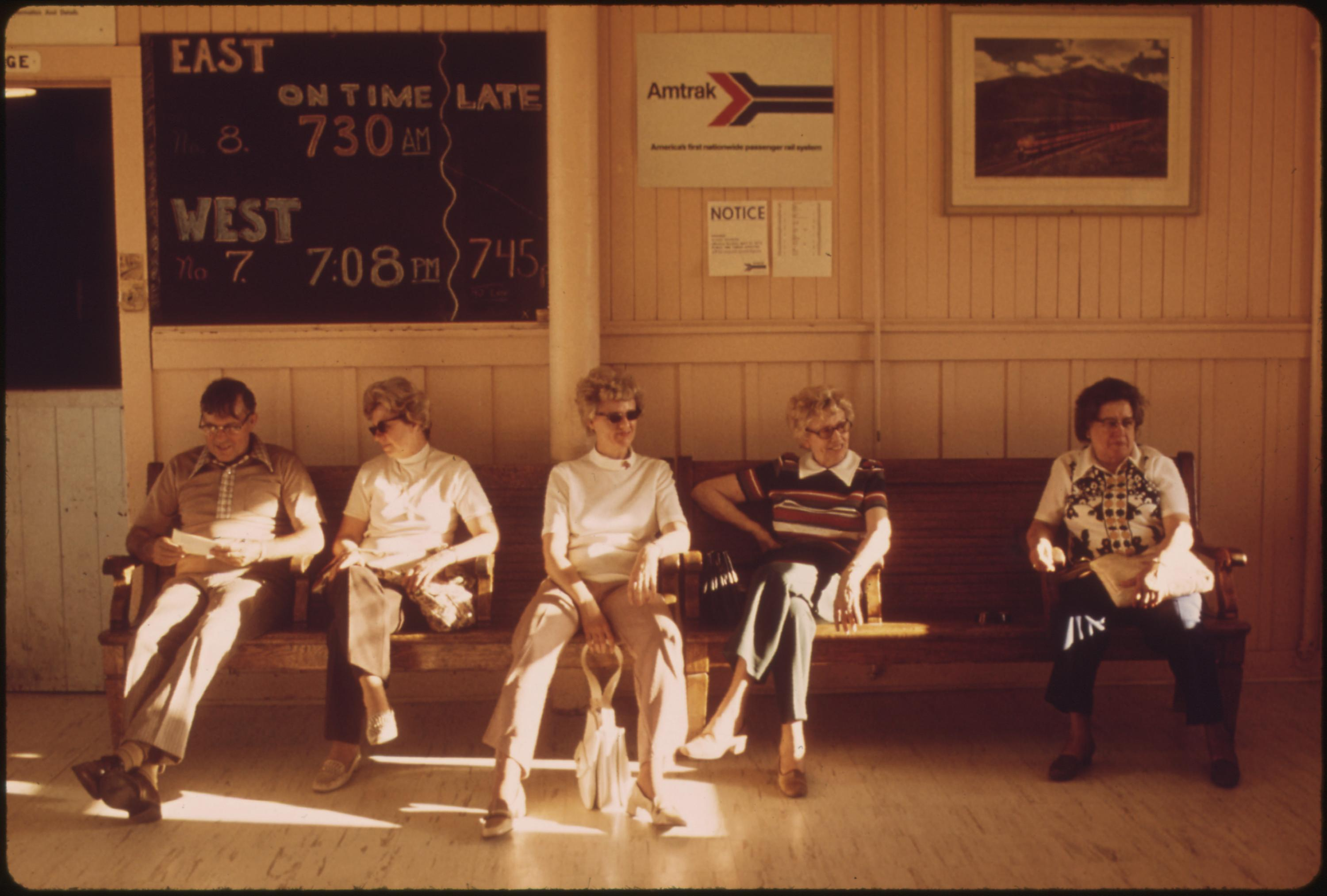 Passengers waiting in the station at East Glacier Park Montana, for the train which will take them to Seattle, Washington, June 1974