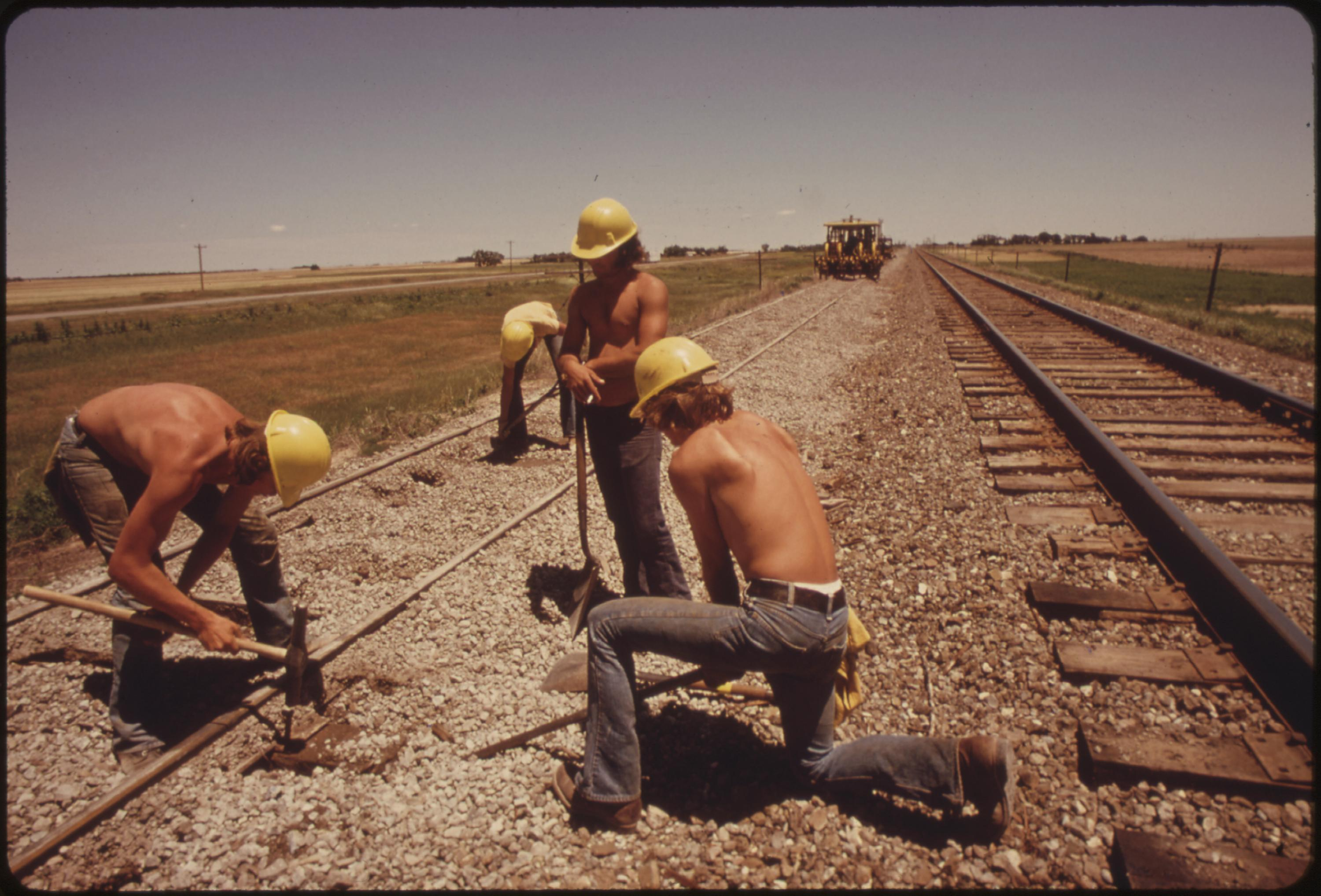 Railroad work crew improves the tracks and bed of the Atchison, Topeka and Santa Fe railroad near Bellefont, Kansas, June 1974