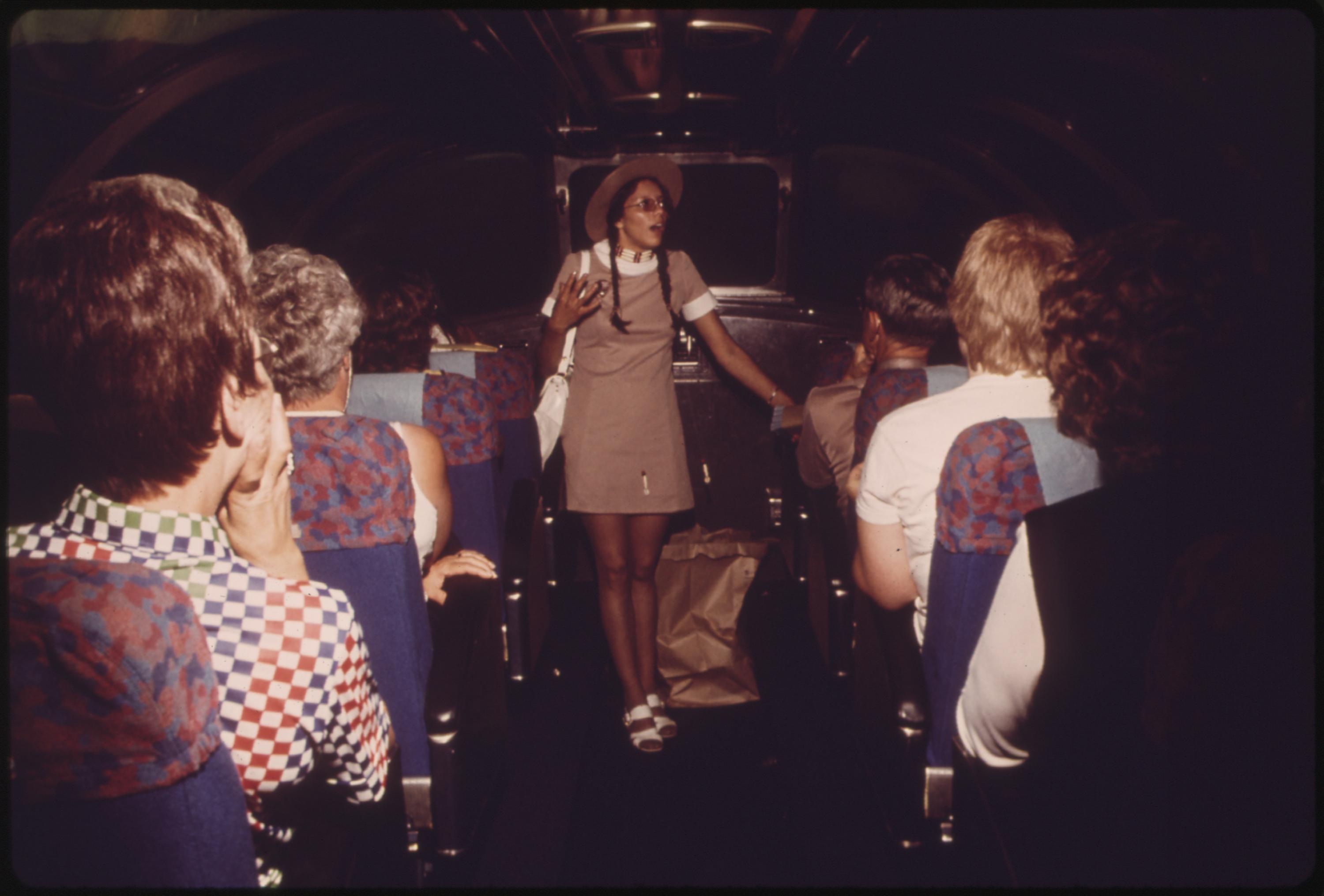 Westbound Empire Builder winds beside Glacier National Park after leaving East Glacier Park, Montana. A park aide describes the surroundings to passengers in the observation car, June 1974