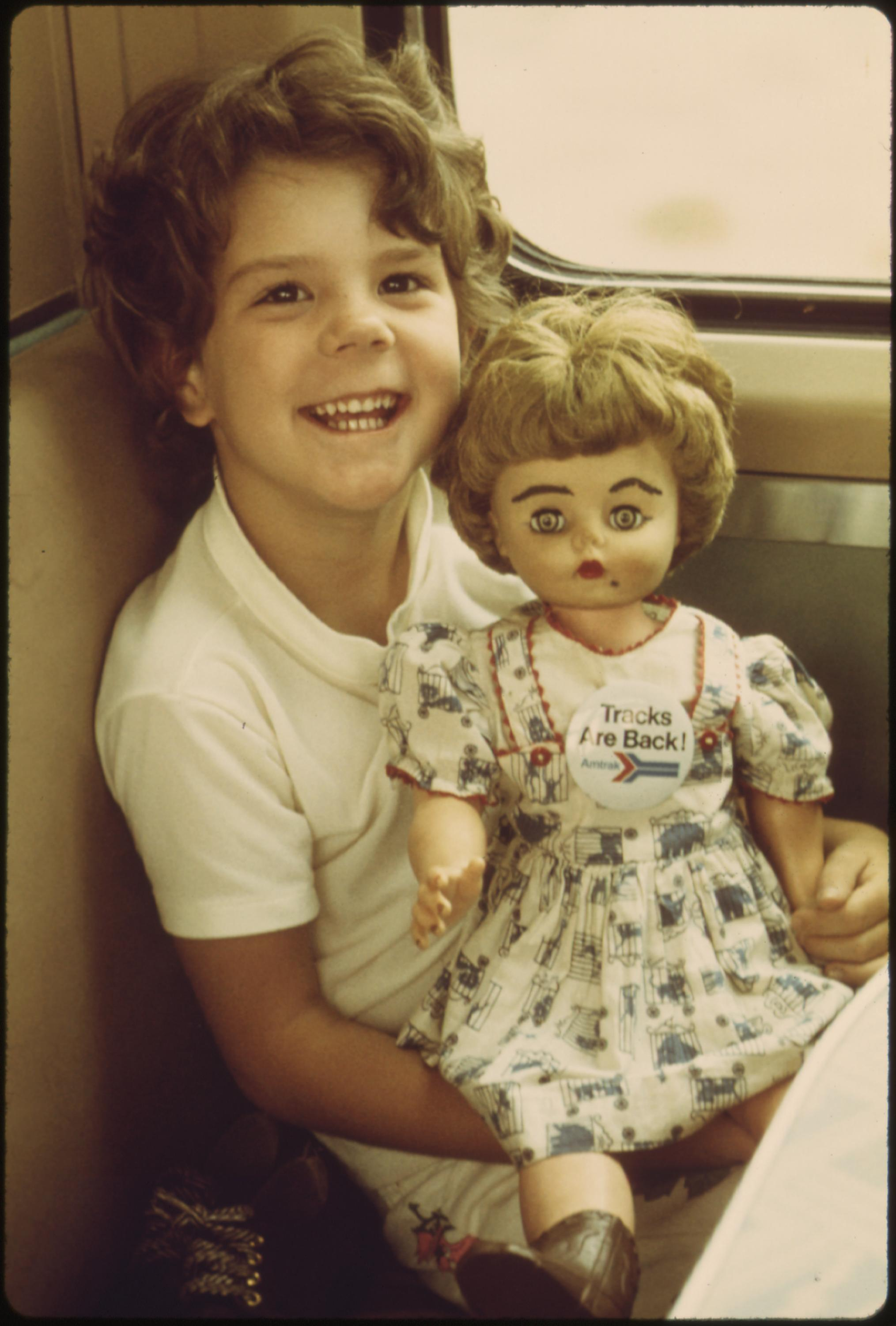 Young girl shows off her doll on the Southwest Limited which sports a pin proclaiming Tracks are Back!, June 1974